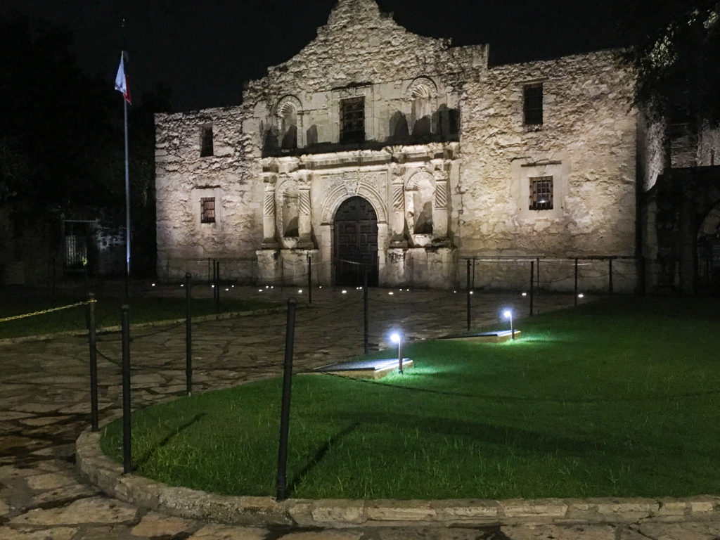 The front of the alamo at night.