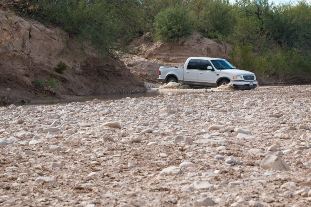 Ford pickup truck crossing river in Mexico.