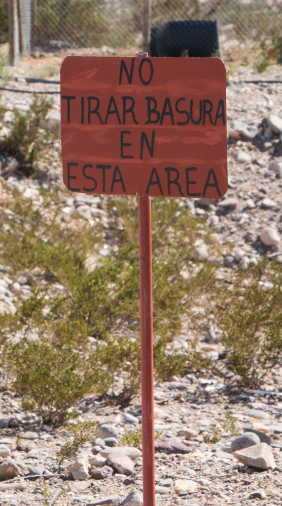 "A sign in Spanish saying ""Don't throw garbage in this area."""